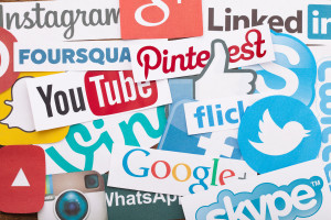 KIEV UKRAINE - AUGUST 22 2015:Collection of popular social media logos printed on paper:Facebook Twitter Google Plus Instagram Pinterest Skype YouTube Linkedin and others on wooden background