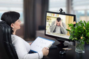 Depressed man is exceedingly despondent at first encounter with virtual psychotherapist. The man sits with his head in his hands. Black-haired glasses psychotherapist watches and hears him on monitor. She holds written message- Dont give up.